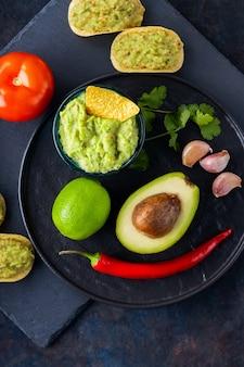 Guacamole-sauce, nachos-chips und zutaten auf dunklem hintergrund. mexikanische guacamole-sauce mit avocado, zutaten und mais-nachos. platz kopieren. ansicht von oben