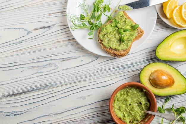Guacamolebestandteile auf holztisch, avocado, zitrone, gewürzen und vollkornbrottoast