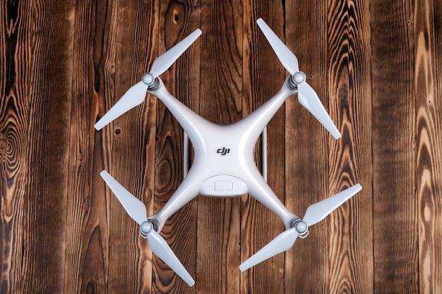 Guadcopter-drohnen - phantom 4 pro + lokalisiert auf einem hölzernen hintergrund