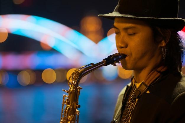 Guangzhou, china - 15. märz 2016: mann, der saxophon auf der straße am abend spielt