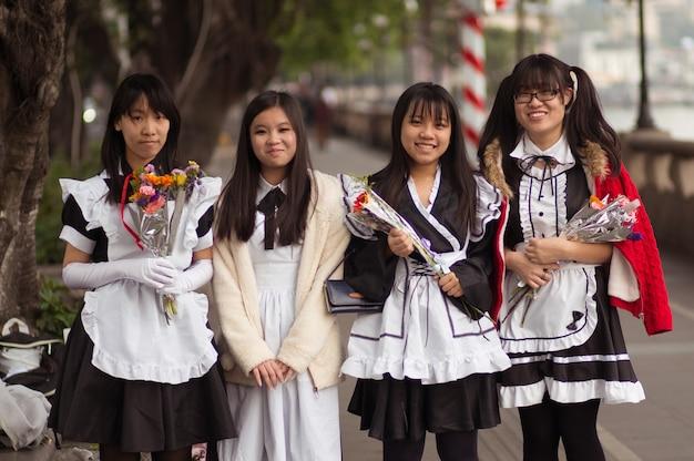 Guangzhou, china - 15. märz 2016: vier lächelnde hübsche studentenmädchen des chinesen in der schulabnutzung mit blumen