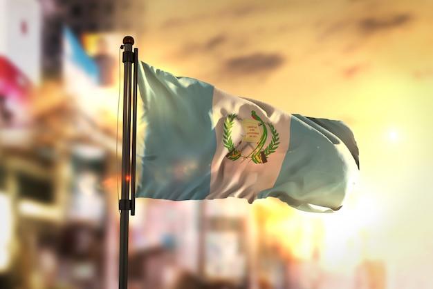 Guatemala-flagge gegen stadt verschwommen hintergrund bei sonnenaufgang hintergrundbeleuchtung