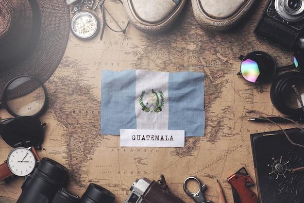 Guatemala-flagge zwischen dem zubehör des reisenden auf alter weinlese-karte. obenliegender schuss