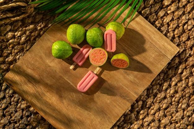 Guava-eis am stiel mit grava-früchten auf holzsockel, sonnenlicht, palmblatt, draufsicht