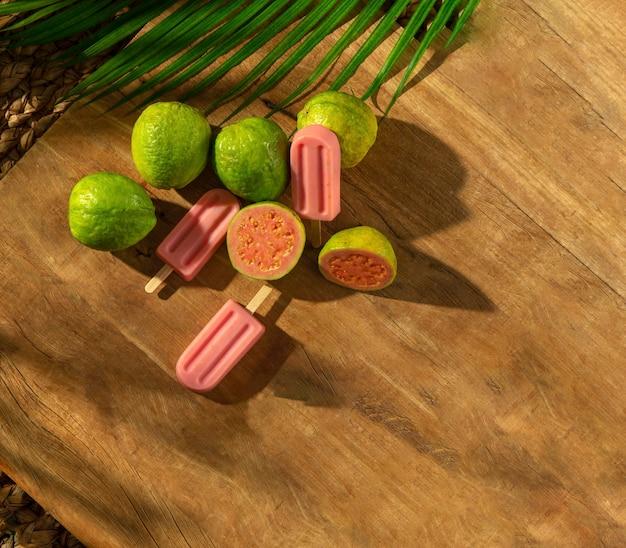 Guava-eis am stiel mit grava-früchten auf holzsockel, sonnenlicht, palmblatt, draufsicht Premium Fotos