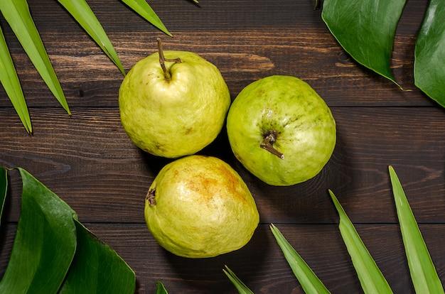 Guave auf dem hintergrund der grünen palmblätter.