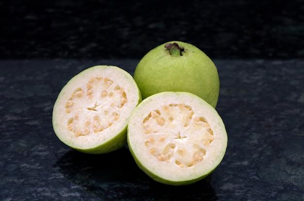Guave, ganz und in scheiben geschnitten, auf granitoberfläche