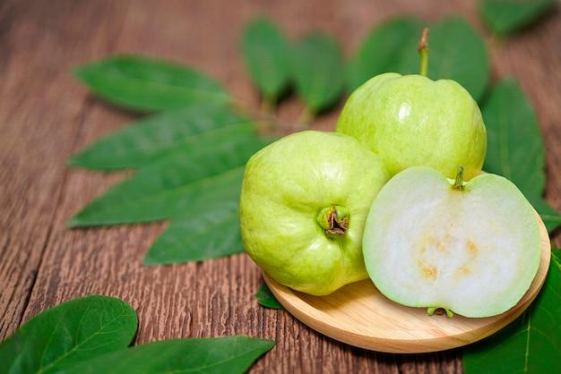 Guavenfrucht mit blatt auf einem holztisch, guavenfrucht auf dem braunen holztisch.