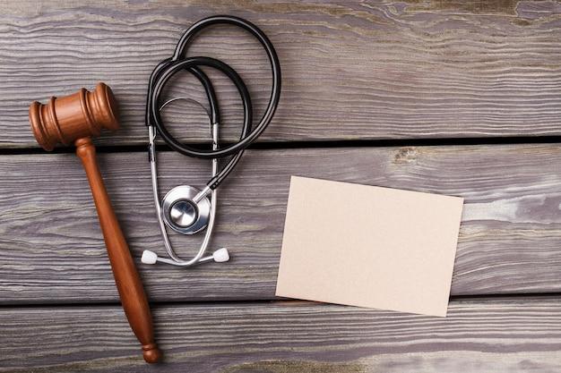 Gudgement und gesundheitskonzept. hammer mit stethoskop und umschlag auf holz. draufsicht flach liegen.