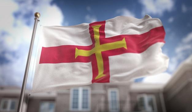 Guernsey-flagge 3d-rendering auf blauem himmel gebäude hintergrund
