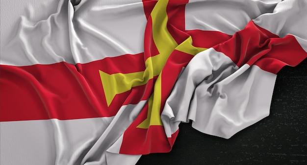 Guernsey-flagge, die auf dunklem hintergrund verstreut ist 3d render
