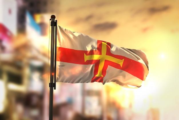 Guernsey-flagge gegen stadt verschwommen hintergrund bei sonnenaufgang hintergrundbeleuchtung