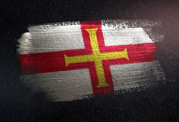 Guernsey-flagge gemacht von der metallischen bürsten-farbe auf dunkler wand des schmutzes