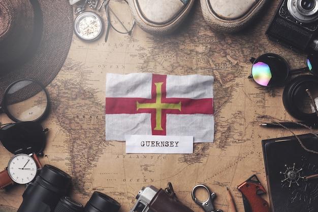 Guernsey-flagge zwischen dem zubehör des reisenden auf alter weinlese-karte. obenliegender schuss