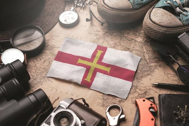 Guernsey-flagge zwischen dem zubehör des reisenden auf alter weinlese-karte. touristisches bestimmungsort-konzept.