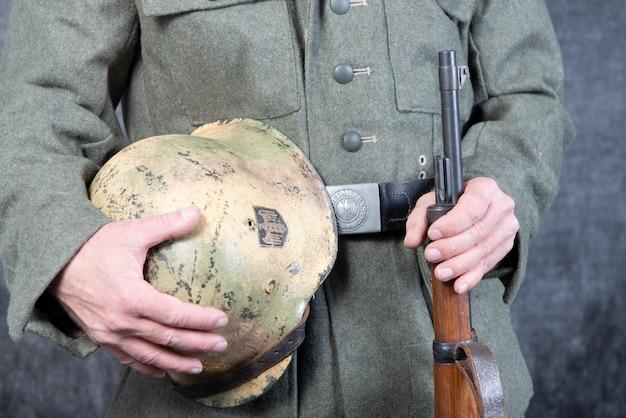 Gürtel und helm des deutschen soldaten in jacke des zweiten weltkriegs
