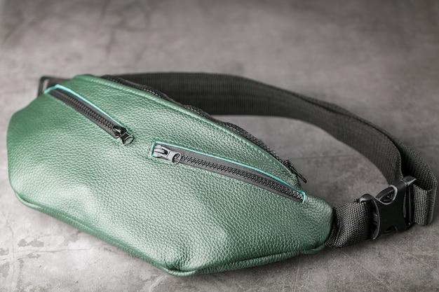 Gürteltasche aus dunkelgrünem strukturiertem leder auf grau