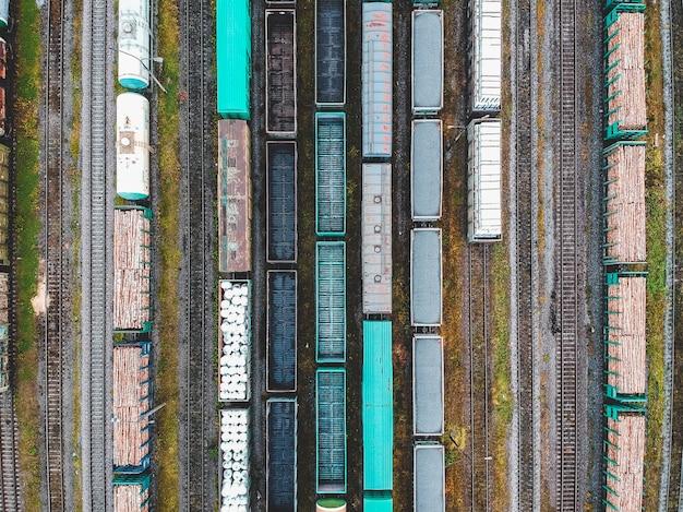 Güterzüge. vogelperspektive von bunten güterzügen auf dem bahnhof. wagen mit waren auf der eisenbahn. schwerindustrie. industrielle begriffsszene mit zügen. blick vom fliegenden drohne.