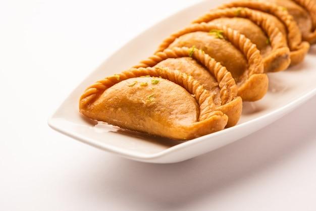 Gujiya oder gujia oder karanji. süße teigtaschen, die während des holi- und diwali-festes zubereitet werden, serviert auf einem teller