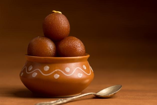Gulab jamun im tontopf. indisches dessert oder süßes gericht