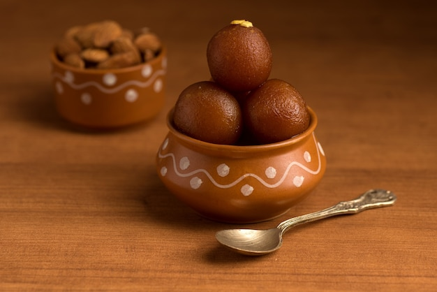 Gulab jamun im tontopf mit löffel und trockenen früchten. indisches dessert oder süßes gericht