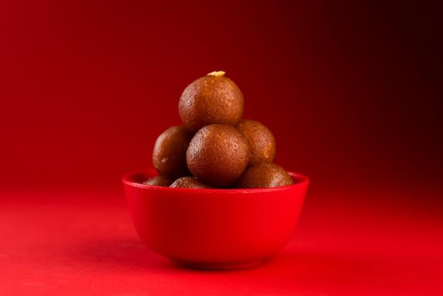 Gulab jamun in der roten schüssel auf rotem hintergrund. indisches dessert oder süßes gericht.