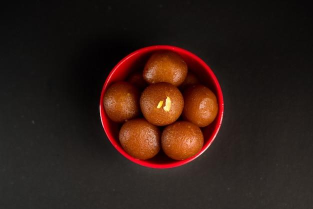 Gulab jamun in der schüssel auf schwarzem hintergrund. indisches dessert oder süßes gericht.