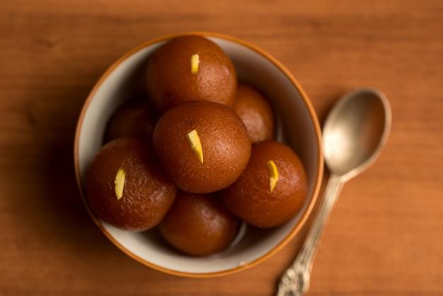 Gulab jamun in schüssel auf holz. indisches dessert oder süßes gericht.