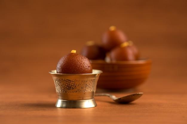 Gulab jamun in schüssel und kupfer antike schüssel mit löffel. indisches dessert oder süßes gericht.