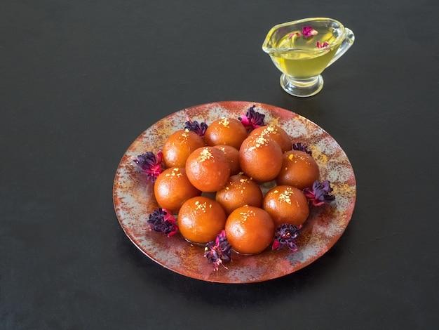 Gulab jamun - traditionelle indische süßigkeiten auf einem schwarzen tisch