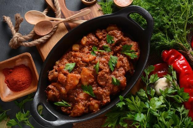 Gulasch traditioneller ungarischer rindfleischeintopf oder suppe mit gemüse und tomatensauce