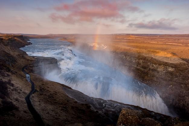 Gullfoss-wasserfall in island-sonnenuntergang mit regenbogen und bewölktem tag