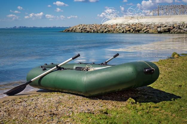 Gummiboot mit angelausrüstung stehend auf einem fluss nahe dem sandstrand.