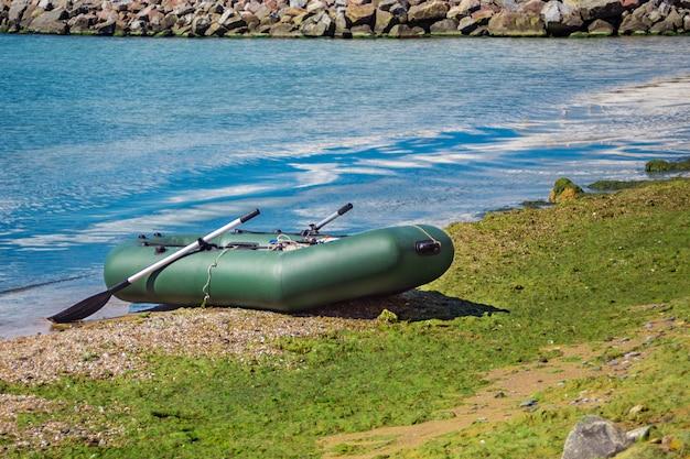 Gummiboot mit der fischereiausrüstung, die auf einem fluss nahe dem sandigen strand steht.