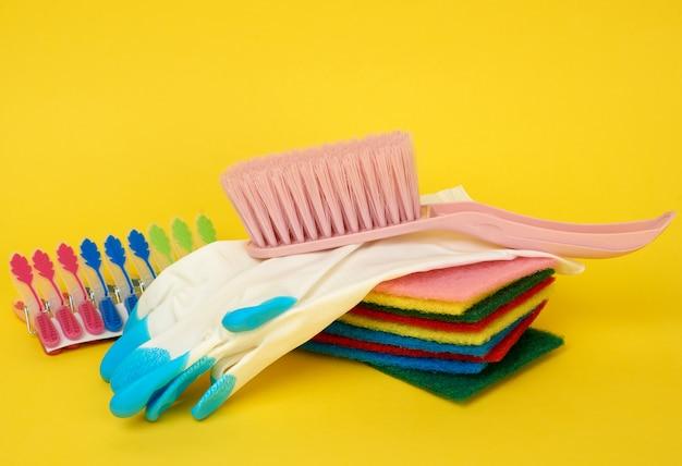 Gummihandschuh und schwarze plastikbürste zur reinigung des hauses