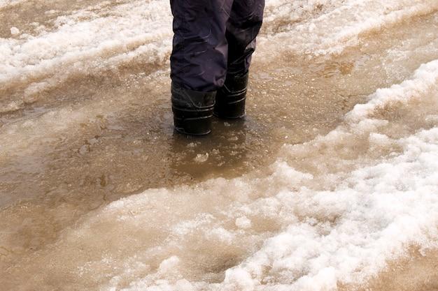 Gummistiefel in pfützen in der stadt bei nassem wetter. regen, schnee und hagel, in der stadt ist es besser, in zuverlässigen schuhen zu laufen