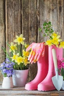 Gummistiefel und frühlingsblumen an holzwand