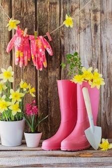 Gummistiefel und frühlingsblumen auf hölzernem hintergrund