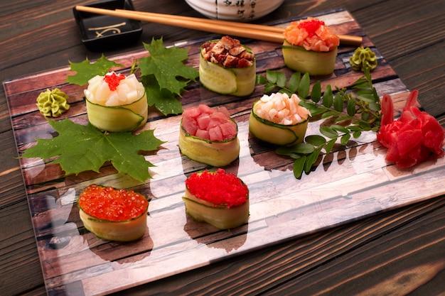 Gunkan maki in einer gurke, mit kaviar, thunfisch. jakobsmuschel, aal, garnele, aal und lachs auf einem holzbrett