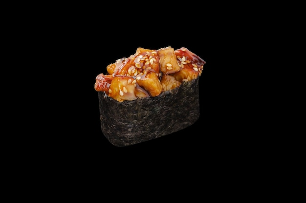 Gunkan maki sushi mit würzigem aal, sesam, würziger sauce, reis isoliert auf schwarz