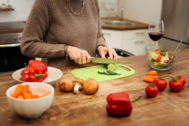 Gurke hacken. konzentrierte, fitte reife frau, die gemüse für gesunden salat schneidet und wein trinkt