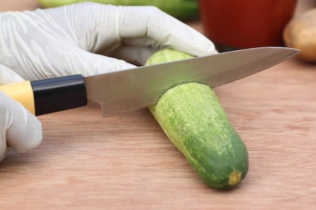 Gurke mit einem küchenmesser auf holzunterlage schneiden