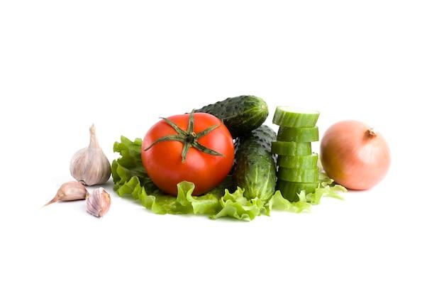 Gurke mit tomaten auf einem weißen hintergrund. gemüse auf einem weißen hintergrund. frisches mehrfarbiges gemüse auf weißem hintergrund. tomate mit zwiebeln und gurken auf einem weißen hintergrund.