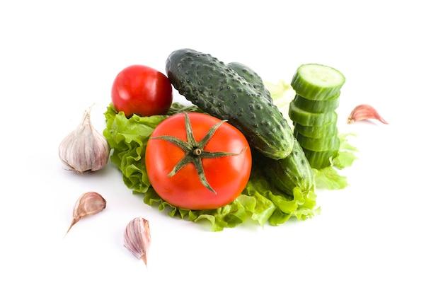Gurke mit tomaten auf einem weißen hintergrund. gemüse auf einem weißen hintergrund. frisches mehrfarbiges gemüse auf weißem hintergrund.