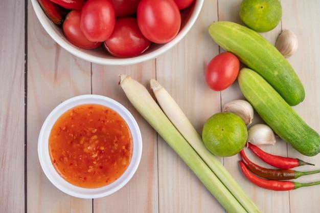 Gurke, zitrone, tomate, knoblauch, chili mit sauce auf dem holzboden.