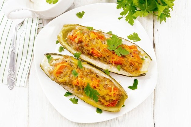 Gurken gefüllt mit hackfleisch, tomaten, pfeffer mit käse und petersilie in einem teller, sahne- und grünsoße in einer sauciere, handtuch auf dem hintergrund eines hellen holzbretts von oben