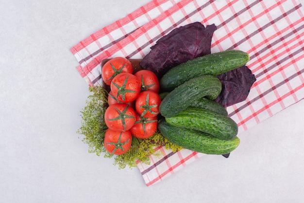 Gurken, gemüse und tomaten auf tischdecke.