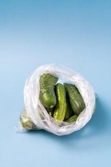 Gurken in der plastiktasche auf blauem hintergrund. verwenden sie keine aufbewahrungsbeutel für künstliche lebensmittel mehr.