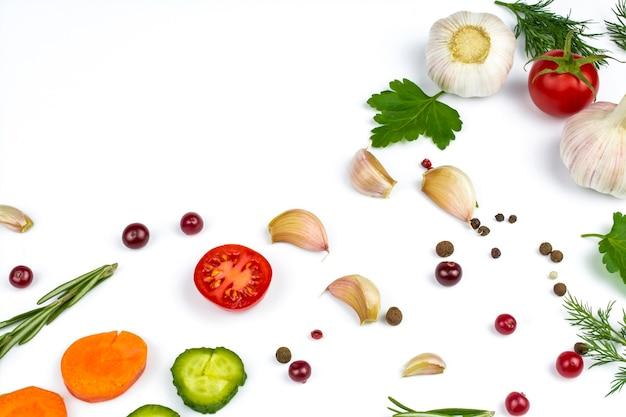Gurken, karotten, beeren und gemüse, knoblauch und frische tomaten auf weißem hintergrund. platz für text.