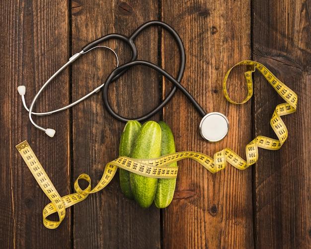 Gurken; maßband und stethoskop auf holzoberfläche